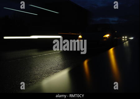 Car broken down on motorway in the dark, awaiting recovery on the hard shoulder. - Stock Image