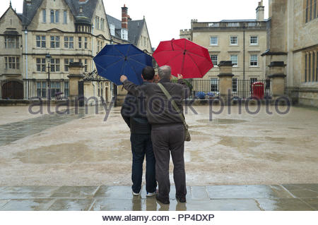 Wet weather - two men, with umbrellas, pose for a selfie beside The Bodleian Library, of Oxford University, city of Oxford, UK. - Stock Image