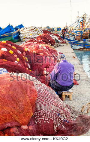Morocco, Marrakesh-Safi (Marrakesh-Tensift-El Haouz) region, Essaouira. Old man repairing fishing nets in the fishing - Stock Image
