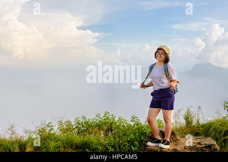 Tourist teens girl hiker with backpack cap and glasses is standing smile and poses happily at high mountain on sky - Stock Image