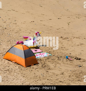 The paraphernalia of a summer seaside holiday - pop-up beach tent, beach towels, and inflatable. - Stock Image