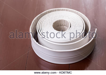 White sanitary sealant strip on the wooden brown table. - Stock Image
