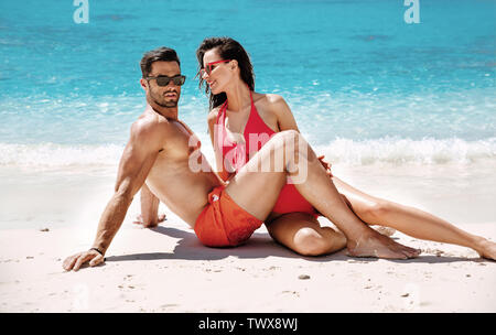 Romantic, young couple relaxing on a tropical beach - Stock Image