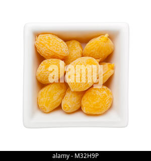 Pieces of preserved peach in a square bowl isolated on white background - Stock Image