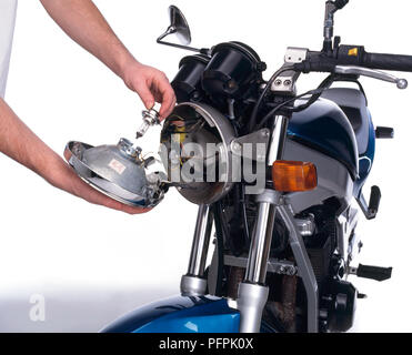 Motorcycle, the lens/reflector unit can be pulled away, the spring clip taken off and the bulb removed. - Stock Image