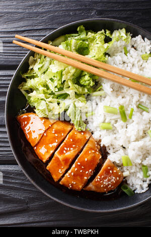Teriyaki chicken with rice garnish and salad close-up on a plate on the table. Vertical top view from above - Stock Image