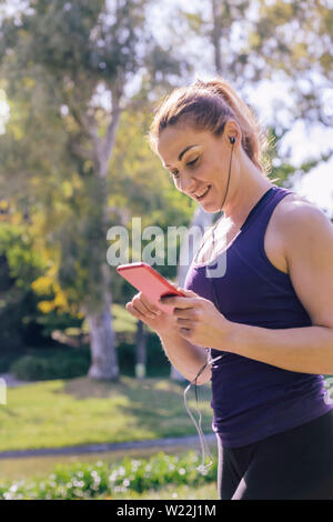 vertical photo of an attractive blonde sports woman listening music before workout outdoors at park, fitness accessories - Stock Image
