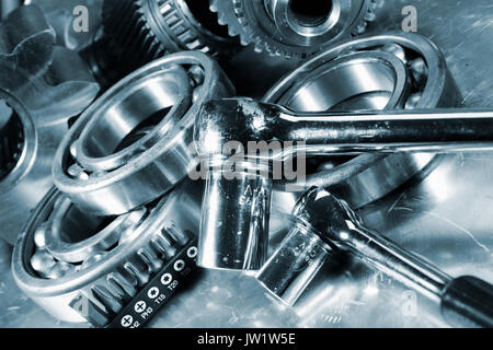 spanners with machine parts and tools, blue toning - Stock Image