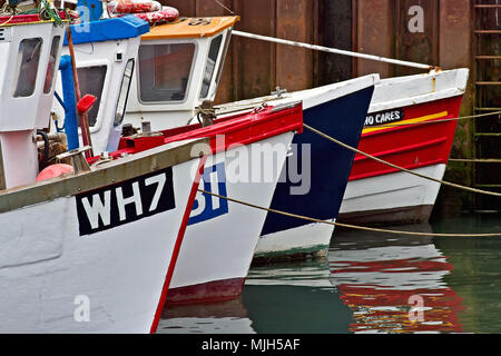 Four small fishing boats form a geometrical alignment in Scarborough harbour. - Stock Image