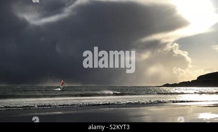 Lone wind surfer under a stormy sky. - Stock Image