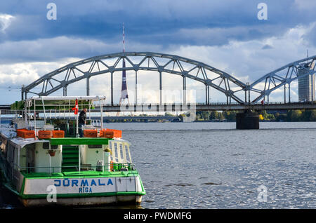 Latvian Railway train passing over the Railway bridge, Riga, Latvia, over the Daugava river, with the Radio and TV tower in the background - Stock Image