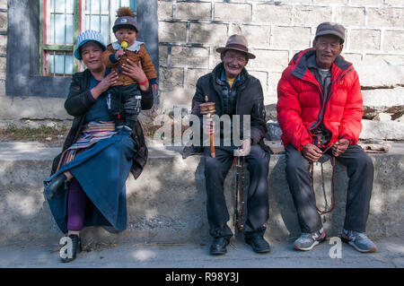 Three adults and an infant relaxing in the Tibetan quarter of Tsetang, Tibet, China - Stock Image