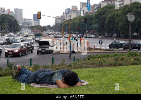 Homeless man sleeping on a grass verge in the middle of Avenida 9 de Julio (B) - Stock Image