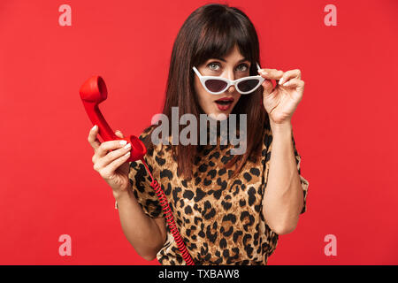 Image of a beautiful young woman dressed in animal printed shirt posing isolated over red background wearing sunglasses talking by telephone. - Stock Image