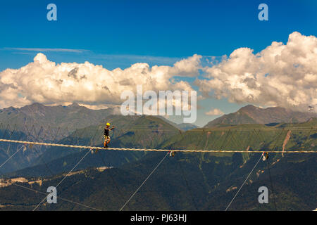 SOCHI, KRASNAYA POLYANA, RUSSIA - JULY 26, 2018: tourist go on a suspended wooden bridge on the mountain top of Rosa Khutor - Stock Image