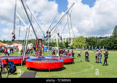 Children bouncing and somersaulting on a bungee trampoline while adults watch at the annual Bradford on Avon Lions funday - Stock Image