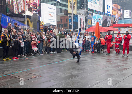 Acrobat gymnastic buskers performing for a crowd of tourists on a rainy weekend morning. Times Square, Manhattan, New York City. - Stock Image