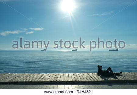 Relaxing on the waterfront in winter sunshine, in the city of Thessaloniki, Central Macedonia, Greece. - Stock Image