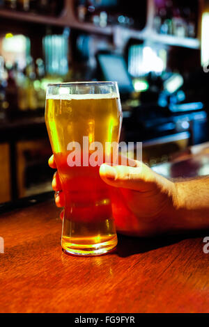 Beer glass being held by male hand at a pub bar - Stock Image