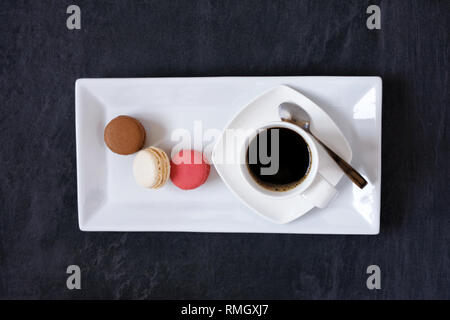 Cup of coffee and three macarons. - Stock Image