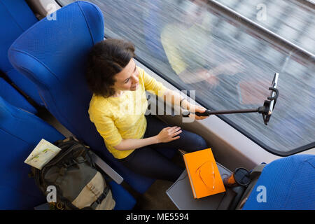 Young woman making selfies with smartphone during traveling in train sitting near window view from above - Stock Image