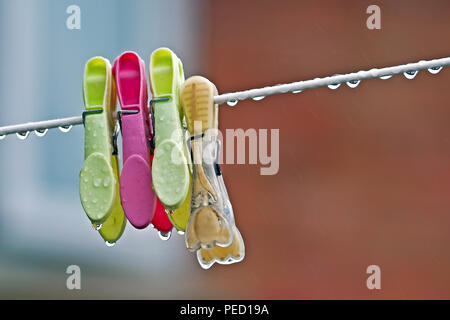 Four clothes pegs hang forlornly on a dripping wet washing line - Stock Image