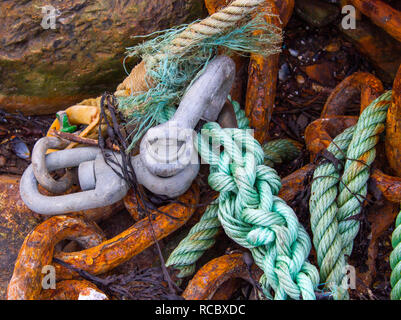 swivel shackle spliced to a rusty chain with green nylon rope. - Stock Image