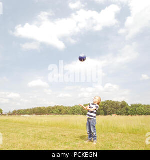 boy,throwing,ball game - Stock Image