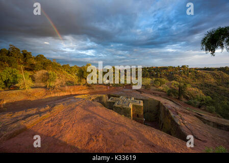 Rainbow set against a grey stormy sky, as golden sunset light catches the top of the ancient stone-carved Bet Giyorgis (Church of St. George), Lalibela, Ethiopia - Stock Image