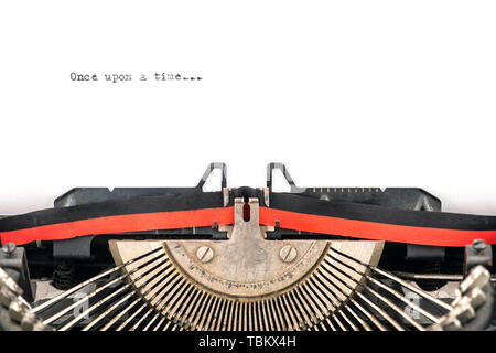 close view of vintage typewriter type bars ready to type a new story on a sheet  beginning with once upon a time - Stock Image