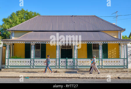 Local pedestrians walking in front of typical Karoo victorian architecture, in Graaff Reinet, South Africa, March 2, 2019 - Stock Image