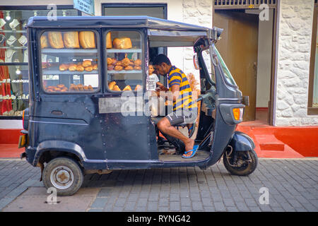 Bread delivery man in black tuktuk in the old part of Galle, under the look of  kid buying . Galle, Sri Lanka, January 9 2018 - Stock Image