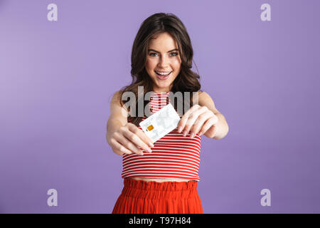 Image of beautiful happy young pretty woman posing isolated over purple background wall holding credit card. - Stock Image