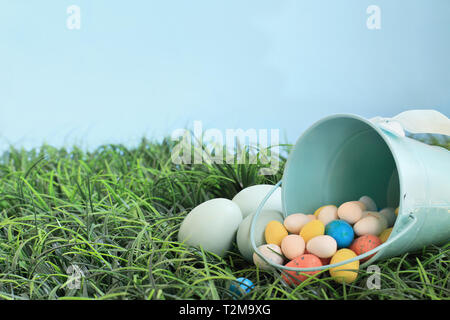 Natural colored Easeter eggs and malt candy eggs spilling from a robin egg blue metal basket in the grass with room for copy space. - Stock Image