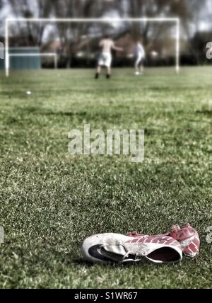 Pair of football boots lying in grass. - Stock Image