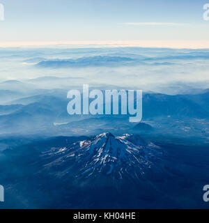 Aerial view of Mt Shasta with smoke surrounding the mountains beyond - Stock Image