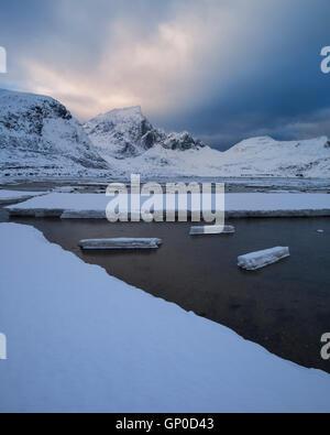 Ice on shoreline at low tide in Flakstadpollen, Flakstadøy, Lofoten Islands, Norway - Stock Image