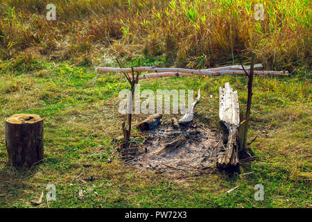 Old fireplace with hemp for sitting in a clearing in the field - Stock Image