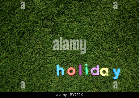 The word 'hello' spelled out in colourful plastic letters, on green grass, taken from a low angle - Stock Image