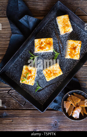 Homemade Creme Brulee cheesecake bars with cream cheese, crushed cookies, topped with caramelized sugar - Stock Image