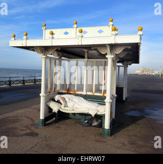 A Homeless man enjoys a cigarette while wrapped up in a sleeping bag from the cold in an Edwardian seafront shelter - Stock Image