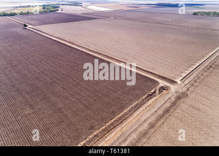 Patches of black and brown soil on flat plains around Moree in Narrabri shire of rural northern NSW part of artesian basin of Australia - elevated aer - Stock Image