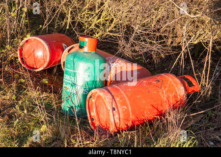 Gas canisters dumped by a footpath - Stock Image
