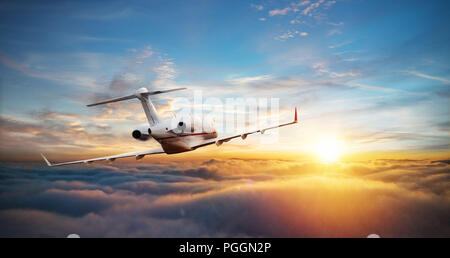 Private jet plane flying above clouds in beautiful sunset light. Modern and fastest mode of transportation, business life. - Stock Image