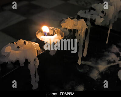 A single burning candle in a church, wax dripping & melting - Stock Image