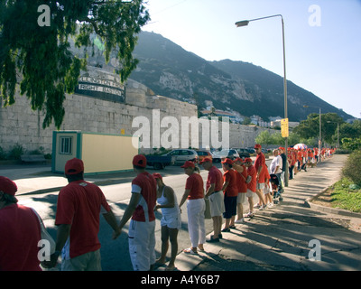 Holding hands around the rock Gibraltar Tercentenary Celebrations human chain hold held link linked hands enjoy Gibraltar - Stock Image