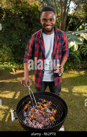 An African man barbecuing - Stock Image