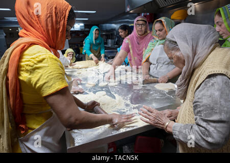 Sikh women of all ages prepare roti breads for their temple's langar (free kitchen). In South Richmond Hills, Queens, New York City. - Stock Image