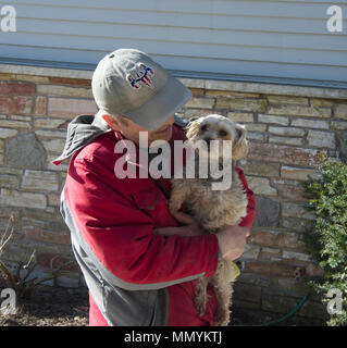 Smiling man holding Yorkshire Terrier dog, Canis lupus familiaris - Stock Image