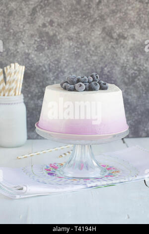 Angel cake on a cake stand with cream and blueberries - Stock Image